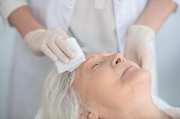 Limpiando una cara. cosmetóloga limpiando la cara de los clientes con una servilleta