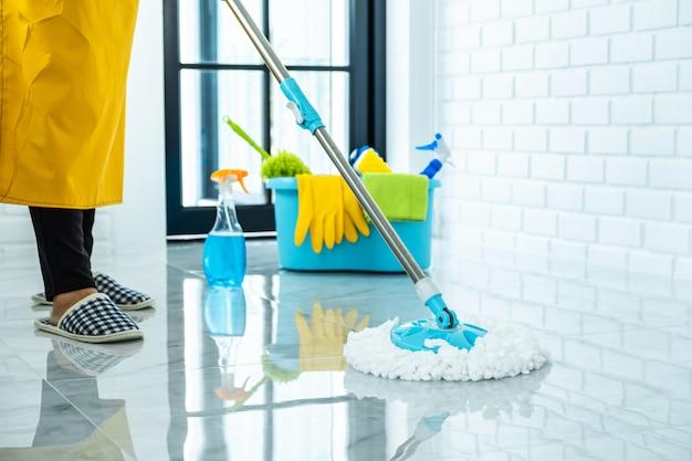 Limpiando el polvo con un trapeador en el piso