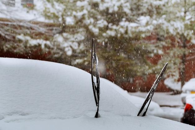 Limpiaparabrisas de un automóvil cubierto de nieve después de fuertes nevadas