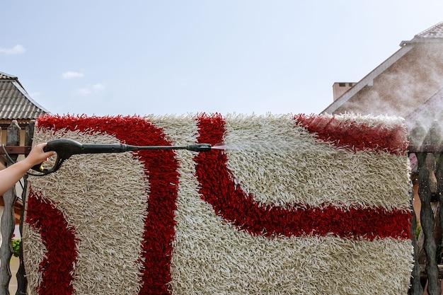 Limpiar la alfombra con pistola para lavar agua a alta presión. limpieza de la casa. al aire libre.