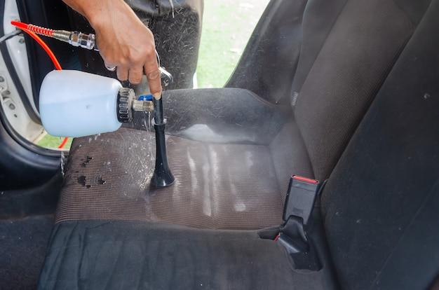 Limpiar el asiento del automóvil con una máquina en un servicio de automóvil
