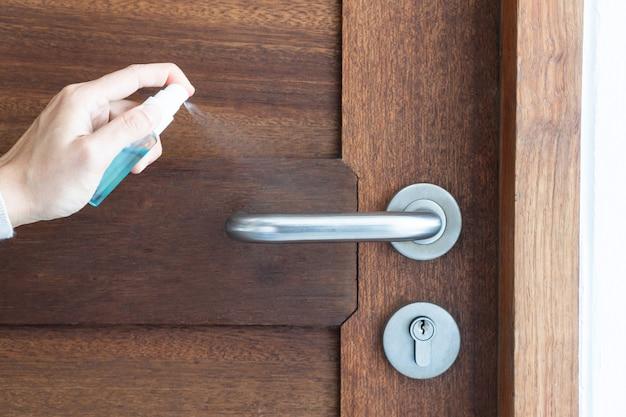 Limpiar la perilla de la puerta con alcohol en aerosol para prevenir el coronavirus. concepto de desinfección covid-19