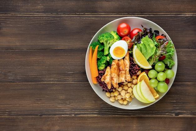 Limpie la comida con una ensalada mixta de verduras y frutas en el fondo de la mesa de madera
