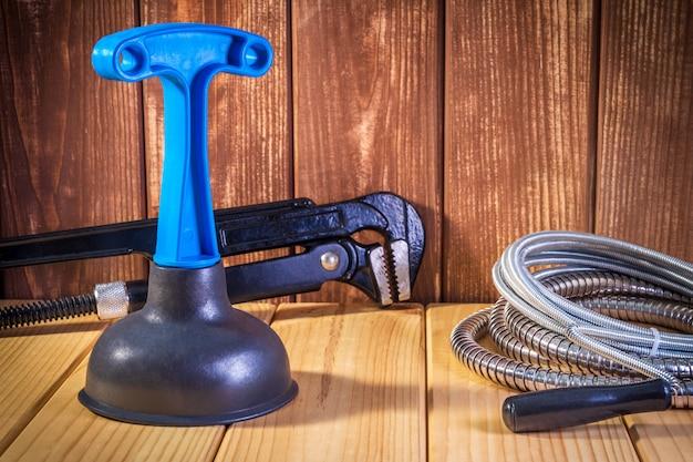 Limpie el émbolo de plástico con mango azul, llave de tubo y cable sobre fondo de madera.