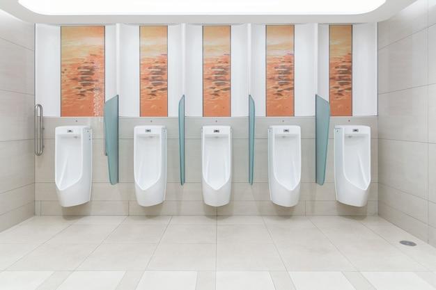 Limpie el inodoro público masculino en el moderno aeropuerto internacional para el servicio a todos los pasajeros