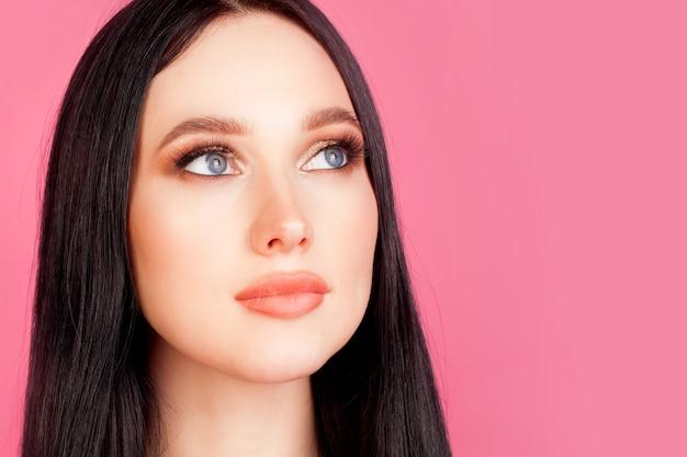 Limpie la piel facial, primer retrato de una mujer en una pared rosa. concept foundation, cosmética y maquillaje, crema facial, limpieza de la piel.