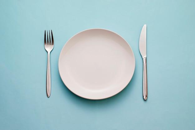 Limpie el plato blanco vacío con cuchillo y tenedor