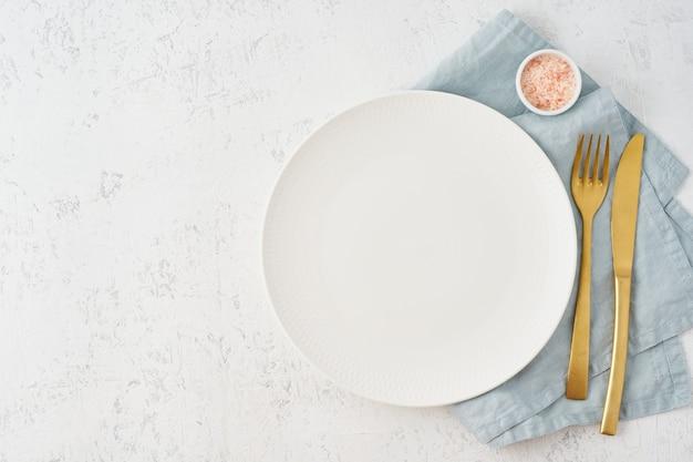 Limpie el plato blanco vacío, tenedor y cuchillo en la mesa de piedra blanca, copie el espacio, simule
