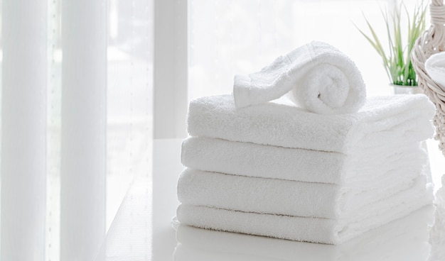 Limpie las toallas blancas en la mesa blanca en la habitación blanca, copie el espacio.