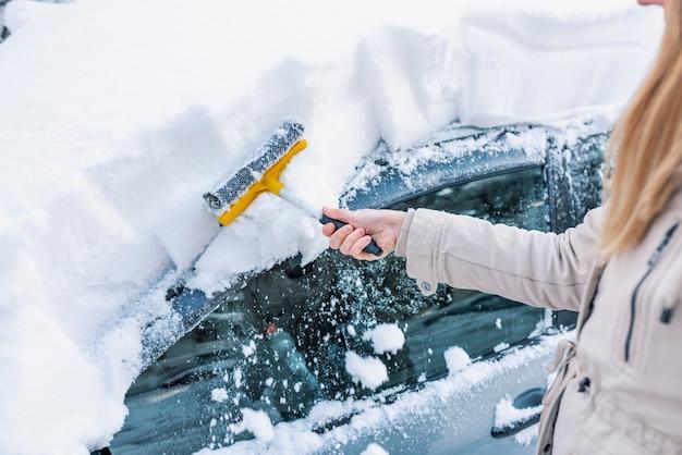 Limpie la ventana del coche de la nieve. limpieza de coches de parabrisas de invierno.