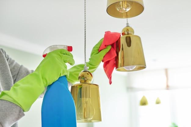 Limpieza de la casa, primer plano de las manos con detergente de trapo, lámpara de limpieza y pulido, lámpara de araña