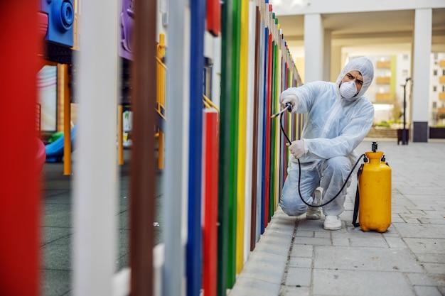 Limpieza y desinfección afuera alrededor del jardín de infantes, la epidemia de covid-19. equipos de sesión para los esfuerzos de desinfección. prevención de infecciones y control de epidemias. e traje y máscara.