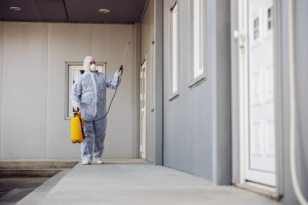 Limpieza y desinfección exterior alrededor de edificios, la epidemia de coronavirus. equipos profesionales para labores de desinfección. prevención de infecciones y control de epidemias. traje protector y mascarilla.