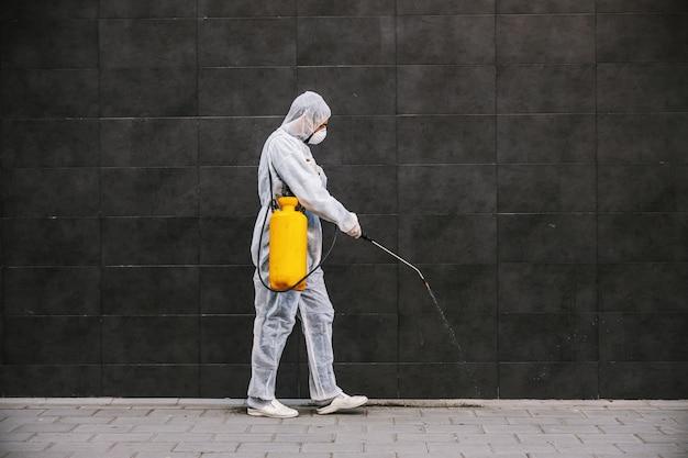 Limpieza y desinfección en el exterior alrededor de los edificios, la epidemia de covid-19. equipos de sesión para los esfuerzos de desinfección. prevención de infecciones y control de epidemias. e traje y máscara.