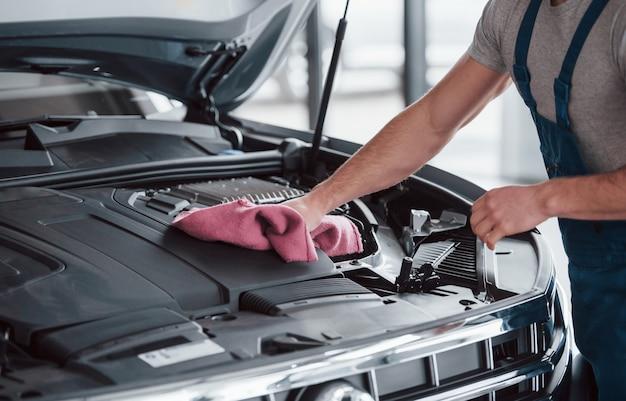 Limpieza después de un buen trabajo. hombre de uniforme azul trabaja con coche roto. haciendo reparaciones