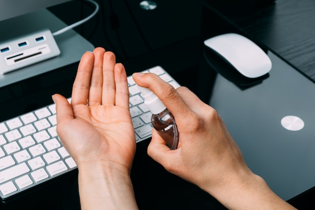 Limpieza de la mano para evitar el virus corona covid 19. spray de alcohol en la computadora portátil para protegerlo de la propagación del virus corona.