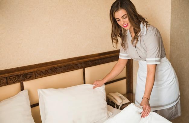 Limpieza de mucama feliz haciendo la cama en hotel.