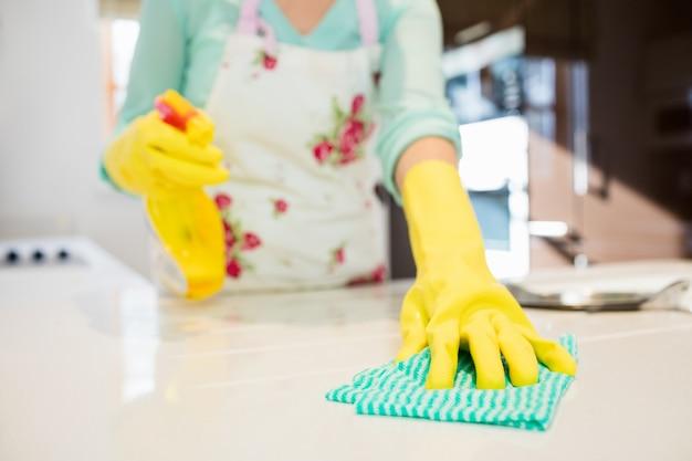 Limpieza de la mujer encimera de la cocina