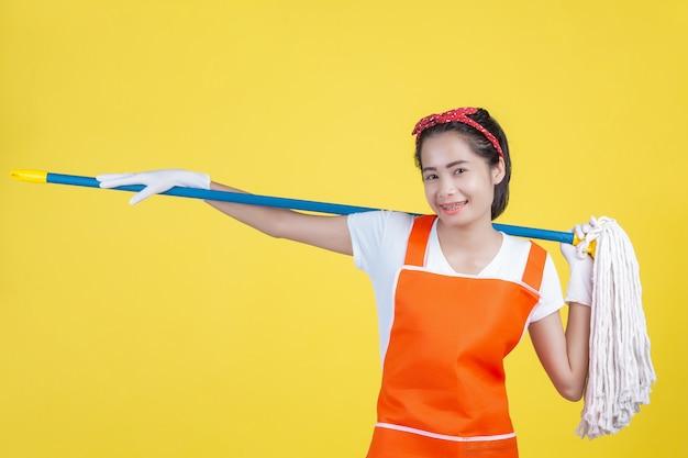 Limpieza una mujer hermosa con un dispositivo de limpieza en un amarillo.