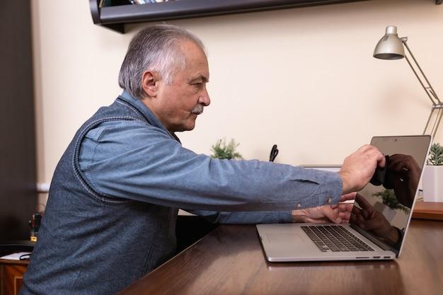 Limpieza de la pantalla del portátil. el hombre limpia la pantalla de la computadora portátil con un paño