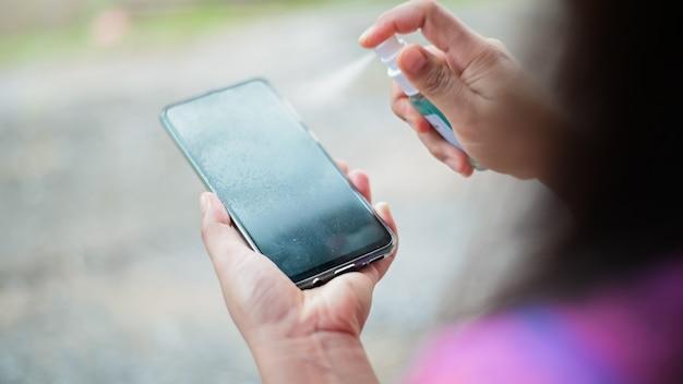 Limpieza de la pantalla del teléfono inteligente con alcohol preventivo covid-19 coronavirus