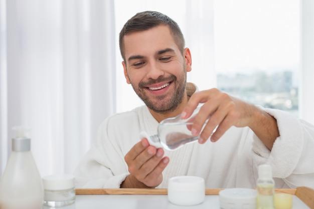 Limpieza de la piel. buen hombre positivo usando una loción para la piel mientras limpia su piel