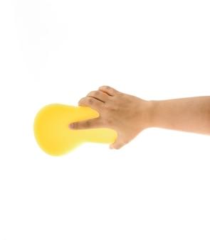 Limpieza del tema de la casa y el saneamiento: mano sosteniendo una esponja amarilla mojada con espuma aislada en blanco