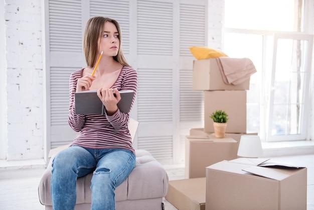 Limpio y organizado. agradable joven sentada en el puf de su antiguo apartamento y comprobar la lista de elementos en el cuaderno antes de mudarse