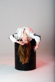 Linda adolescente bailando hip hop en pantalones reflectantes, en un estudio con iluminación de neón. cartel de color de baile.