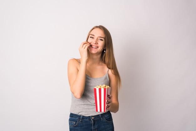 Linda adolescente en una camiseta sin mangas gris sonríe y sostiene callos pop