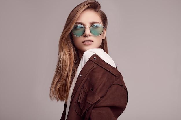 Linda adolescente en chaqueta de moda y gafas de color