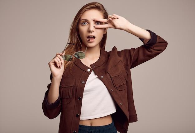 Linda adolescente en chaqueta de moda y gafas