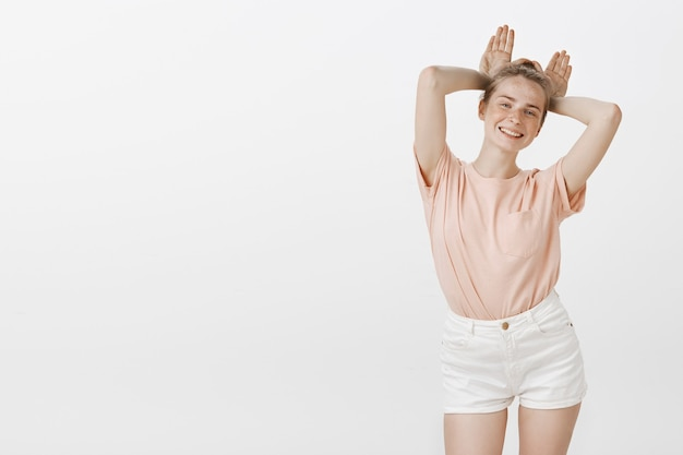 Linda adolescente despreocupada posando contra la pared blanca
