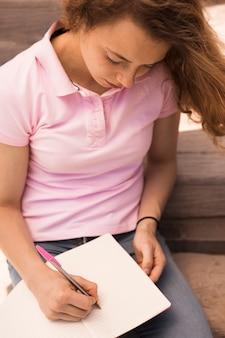 Linda adolescente escribiendo en cuaderno
