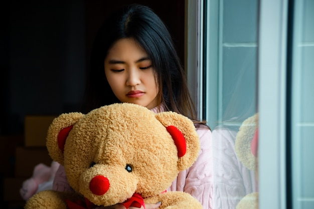 Linda adolescente con gran oso de peluche