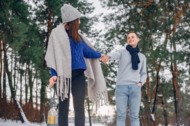 Linda y amorosa pareja en un bosque de invierno