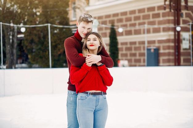 Linda y amorosa pareja en un suéter rojo en una ciudad de invierno