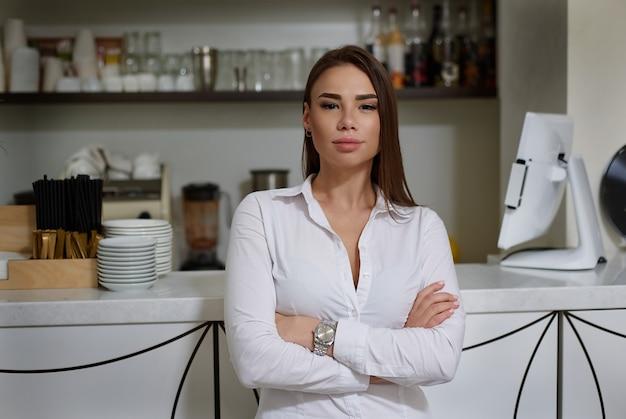 Una linda barista morena con camisa blanca se encuentra en el bar