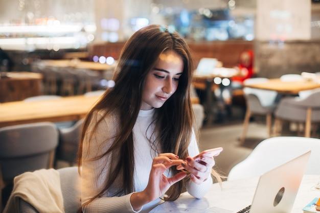 Linda y bastante joven en smartphone en café