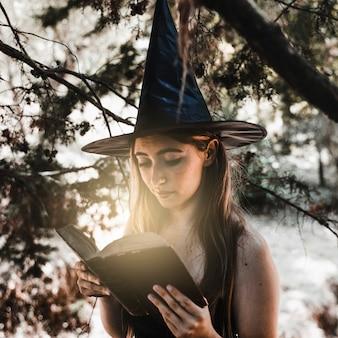 Linda bruja leyendo un antiguo libro de hechizos en un bosque iluminado por el sol
