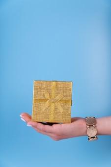 Linda caja de regalo en mano sobre fondo azul.