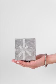 Linda caja de regalo plateada sostenida en la mano