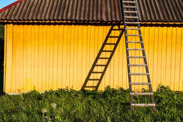Linda casa rural amarilla con escaleras de madera en campo.