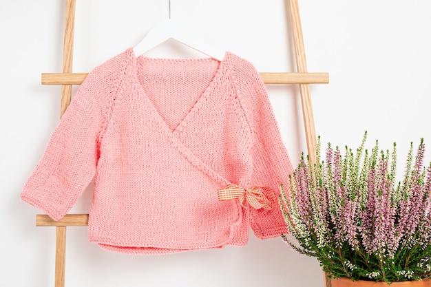 Linda chaqueta de bebé rosa colgada en el perchero