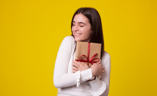Linda chica está abrazando un regalo lleno sobre fondo amarillo.