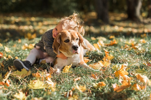 Linda chica abrazando a su mascota en la hierba