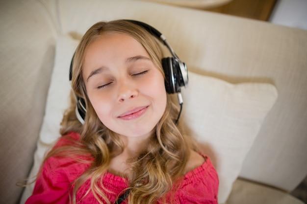 Linda chica acostada en el sofá y escuchando música con auriculares en la sala de estar