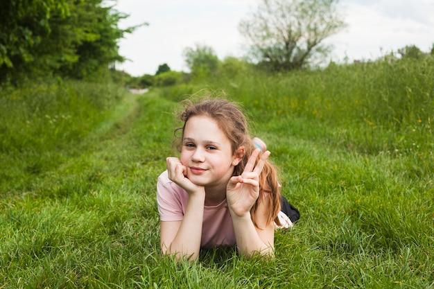 Linda chica acostada en tierra cubierta de hierba que muestra el signo de la victoria en la hermosa naturaleza