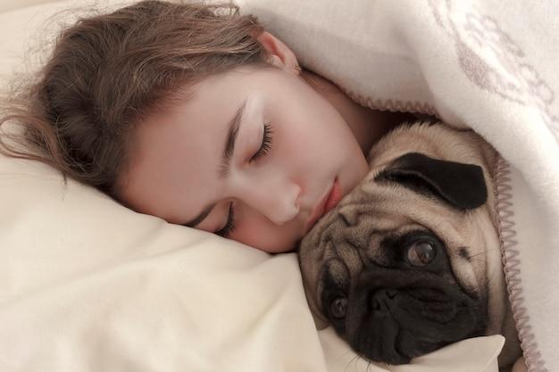 Linda chica adolescente duerme abrazando a un perro pug en la cama