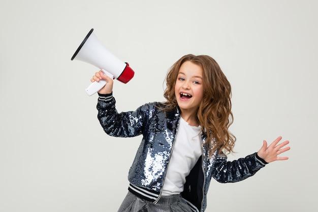 Linda chica adolescente europea con un megáfono informa la noticia